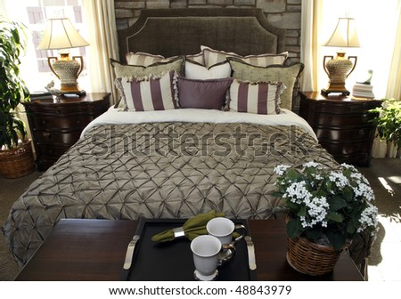 Bedroom with contemporary furniture and decorative pillows. - stock photo