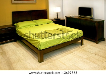 Bedroom with green double bed and LCD TV - stock photo