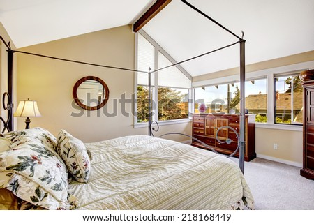 Bedroom with high iron frame bed and vaulted ceiling. - stock photo