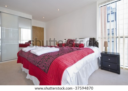 bedroom with king size bed bedside tables reading lamp and built in wardrobe - stock photo