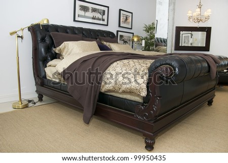 bedroom with leather bed and mirror lamps - stock photo