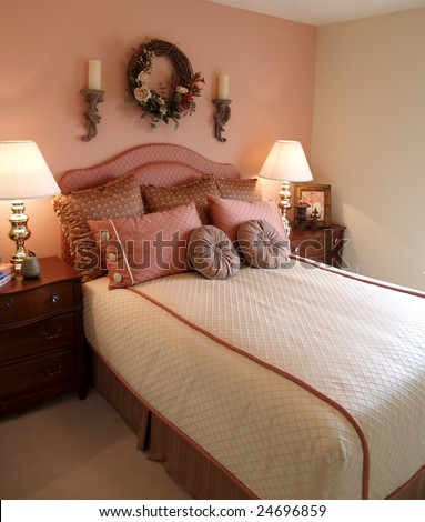 Bedroom with pink accent wall focus on bed and bedding - stock photo