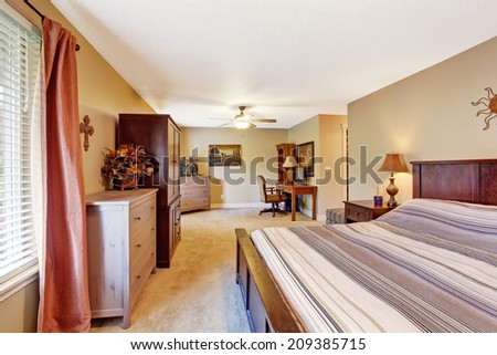 Bedroom with small office area. View of bed in stripes - stock photo