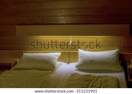 bedroom with two white pillows and light falling on top of bed - stock photo