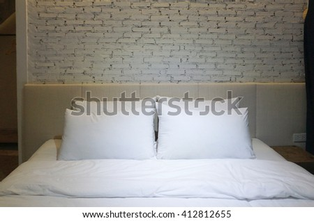 Bedroom with White pillow and bedsheets and white brick background with focus lighting in the middle - stock photo