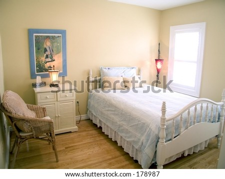 Bedroom with wood floor, white ceiling, window, red lamp, bedside table and throw pillows.