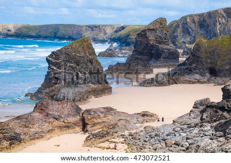 Bedruthan steps in Cornwall, England on low tide with people walking on the beach