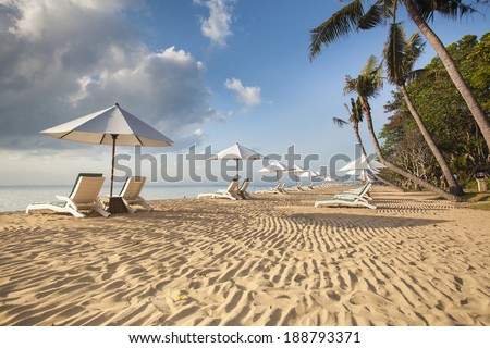 Beds and umbrella on a tropical beach - Bali - stock photo