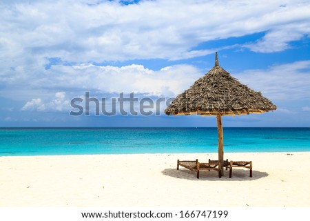 Beds and umbrella on a tropical white sand beach - stock photo