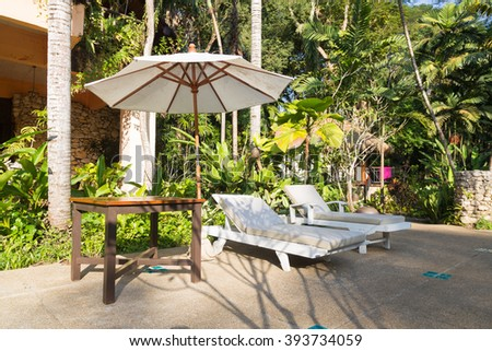 Beds and umbrellas resting on the edge of the pavement, in a garden with trees and relaxing ambience. - stock photo