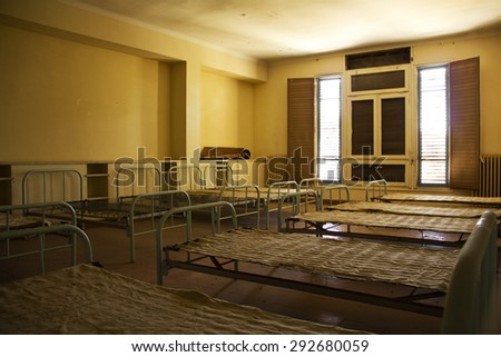 Beds in an abandoned old room in semi darkness - stock photo