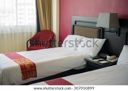 Beds with pillows and table between in luxury hotel room
