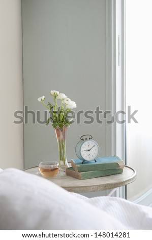 Bedside table with cut flower and alarm clock in bedroom - stock photo