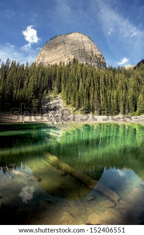 Bee Hive is reflected into Mirror Lake. Lake Louise, Banff National Park, Alberta, Canada.  Mirror Lake is on the way to the Lake Agnes, Tea House, the Bee Hive and places Beyond.  - stock photo