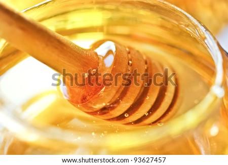 Bee honey with wooden dipper. Honey's dessert - honey stick on golden background. - stock photo