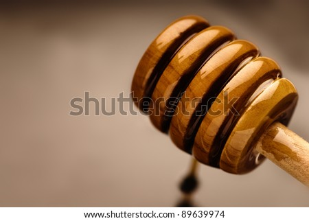 Bee nectar on a wooden honey dripper - stock photo