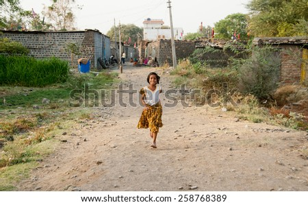 BEED, MAHARASHTRA, INDIA - March 23, 2012: unidentified girl running in rural village Salunkwadi
