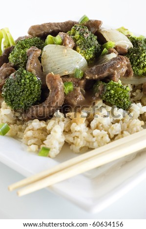Beef and Broccoli and Brown Rice with Chopsticks on White - stock photo