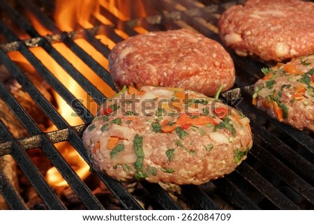 Beef and Pork Burgers On The Barbecue Grill. Flaming Charcoal On the Background. - stock photo
