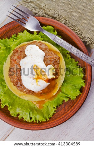 Beef and pork patty with poached egg, smashed potato and lettuce. View from above, top studio shot