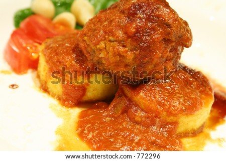 Beef and pork rissole on polenta - stock photo