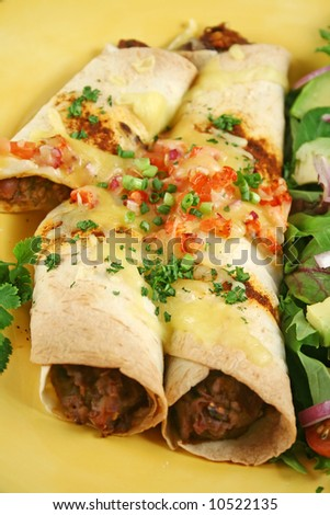 Beef and red kidney bean enchiladas with cheese and salad. - stock photo