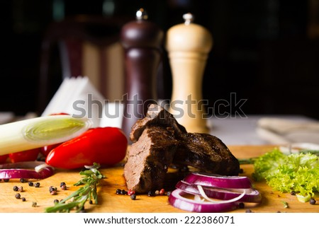 Beef and Vegetables Ingredients for Meal on Cutting Board with Salt and Pepper Mills
