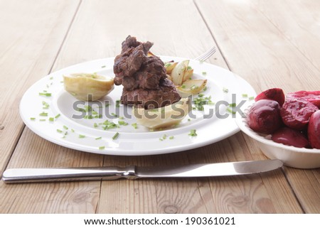 beef bourguignon in wine with artichoke and marinated vegetables on white plate over wooden table - stock photo