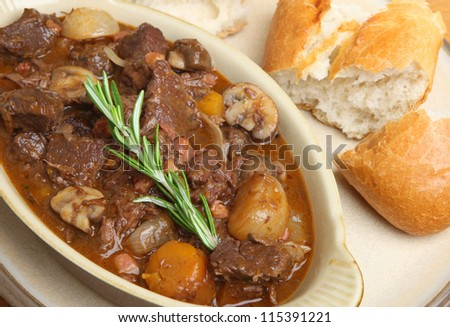 Beef bourguignon served with crusty French bread baguette. - stock photo