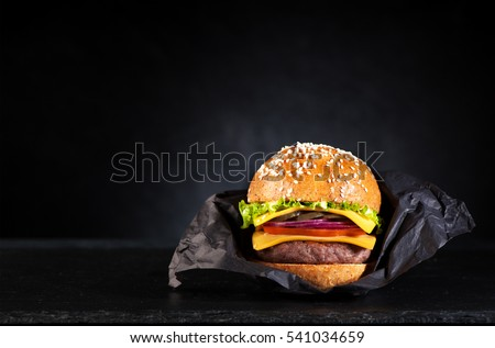 Beef Burger in a paper on a black chalkboard