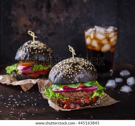 Beef burger with a black bun,with lettuce and mayonnaise and ketchup ...