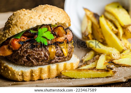 Beef burger with bacon, cheddar, homemade solty fries - stock photo