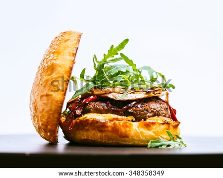 Beef burger with camembert and arugula on white background - stock photo