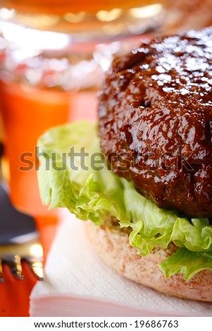 beef burger with fork and beer on background, shallow DOF - stock photo