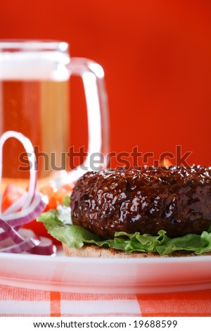 beef burger with onion and beer on red background, shallow DOF - stock photo