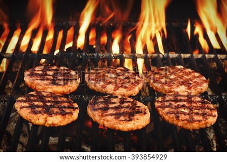 Beef Burgers On The Hot Flaming BBQ Charcoal Grill, Close-up, Top View - stock photo