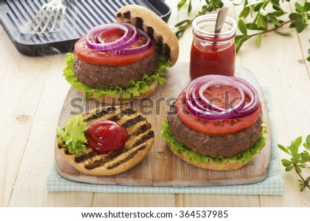 Beef burgers with tomatoes and red onion - stock photo