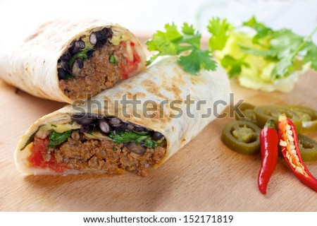 Beef Burrito on wooden board with red chillies peppers  - stock photo