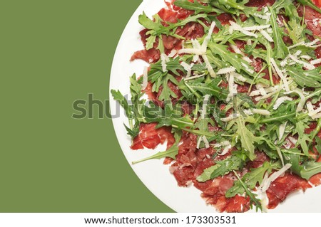 Beef carpaccio in white plate on green background - stock photo