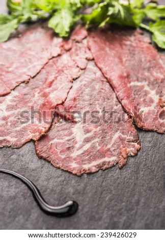 Beef Carpaccio with balsamic on slate background - stock photo