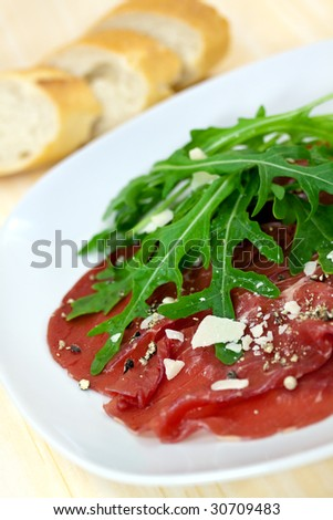 Beef carpaccio with pepper, rucola and parmesan - stock photo