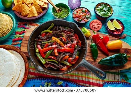 Beef fajitas in a pan with sauces chili and sides Mexican food - stock photo