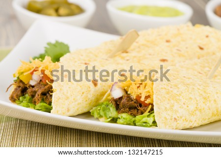 Beef Fajitas - Mexican shredded beef fajitas in soft corn tortillas served with lettuce, sour cream, grated cheddar cheese and salsa.Guacamole, refried beans and jalape�±os on the background. - stock photo