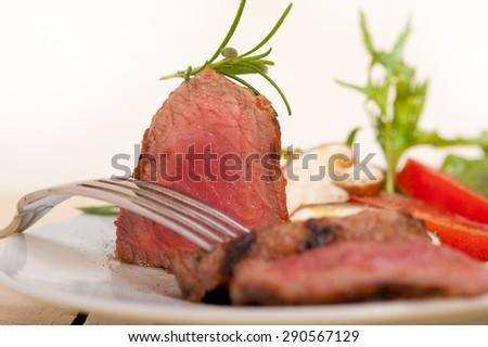 beef filet mignon grilled with fresh vegetables on side ,mushrooms tomato and arugula salad - stock photo