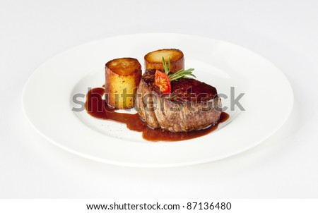 beef filet with fondant potato and red wine sauce on a white plate - stock photo