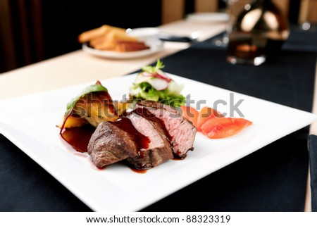 Beef fillet with potato gratin and fresh salad - stock photo