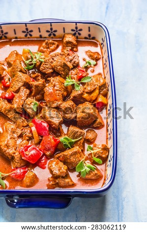 Beef goulash in casserole dish on light wooden background - stock photo