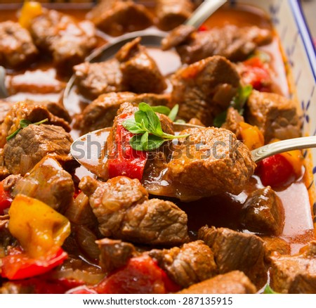 Beef goulash with vegetables and spoon, close up - stock photo