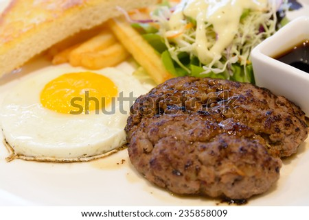 Beef Hamburg steak with egg - stock photo