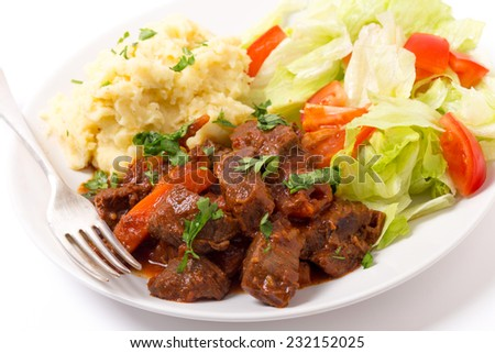 Beef in red sauce with a salad and mashed potato wand a fork - stock photo